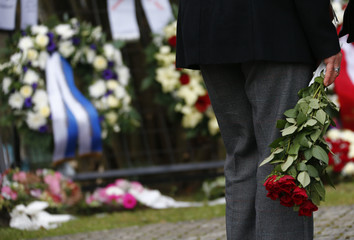 A holds flowers at the cemetry before the burial of late student Tugce Albayrak in Bad Soden-Salmuenster