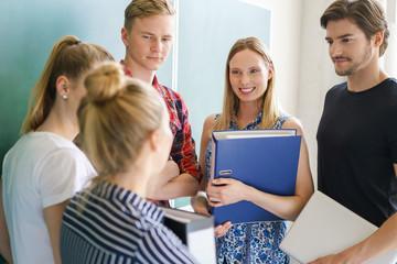 studenten unterhalten sich vor der tafel
