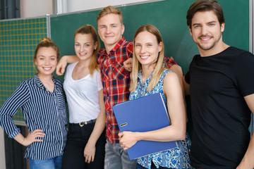glückliche studenten stehen vor der tafel