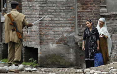 Kashmiri women request that an Indian policeman let them cross a road on the ninth consecutive day of a curfew in Srinagar