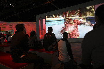 """People watch video graphics from the game """"Dead Island"""" at the Square Enix exhibit during the Electronic Entertainment Expo, or E3 in Los Angeles"""