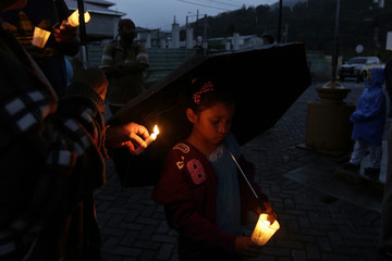 A young local resident holds a candle during a public vigil to find two missing Dutch tourists, in Boquete