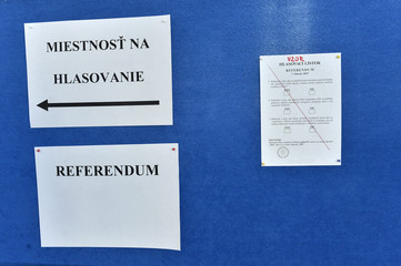 Papers stating instructions and a sample ballot with three questions are displayed on a wall during a referendum to maintain a ban on same-sex marriage, in the village of Vinicne