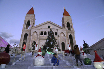 Children pose for photos next to Christmas decorations in front of a church in Jiyeh village