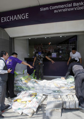 Workers build a wall with sandbags to prevent possible flooding at a bank in Bangkok