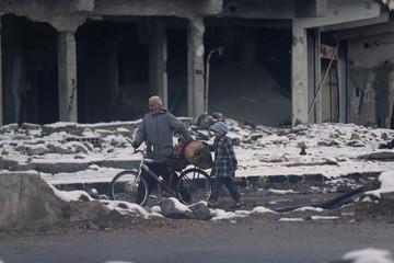 Residents walk through a damaged neighbourhood in Duma, Damascus