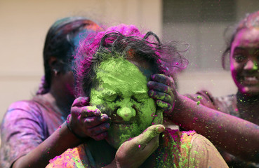 Girls paste abeer, a dye made from various powders, on each other at the Tunapuna Hindu school grounds