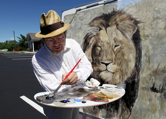 Mark Balma, an international artist based in California and Florence, Italy, paints a lion head on a canvas in the parking lot of River Bluff Dental clinic in protest against the killing of a famous lion in Zimbabwe, in Bloomington, Minnesota