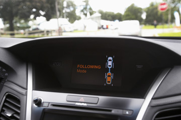 The 'Following Mode' icon is lit on the dashboard screen of an Acura RLX sedan during a demo of Honda's wireless tow technology at the ITS World Congress in Detroit