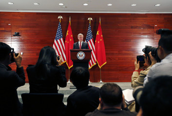 Journalists and staff take pictures as U.S. Ambassador to China Baucus gestures in front of Chinese and American national flags during a news conference at the U.S. Embassy, upon his arrival to his new post, in Beijing