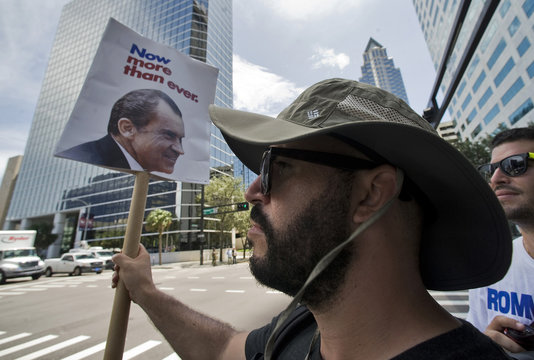 A Republican party supporter holds a vintage Nixon campaign poster on a downtown street corner outside the Republican National Convention in Tampa