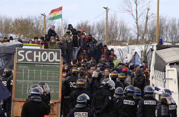 "French riot police face off with migrants and their supporters outside a makeshift school during the partial dismantlement of the camp for migrants called the ""jungle"", in Calais"