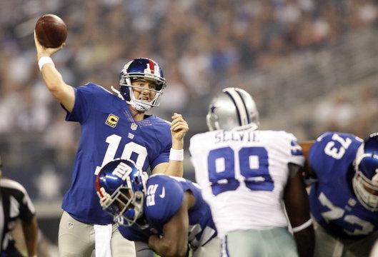 New York Giants quarterback Eli Manning passes as Dallas Cowboys defensive end George Selvie rushes in Arlington, Texas