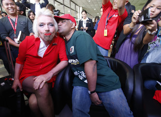 AirAsia's Chief Executive Fernandes pretends to kiss British entrepreneur Branson during an AirAsia promotional event after Branson arrived at an airport in Sepang