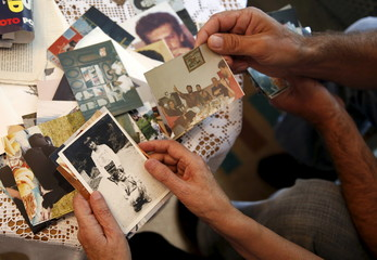Catic and Jakubovic look at pictures at her home in Srebrenica