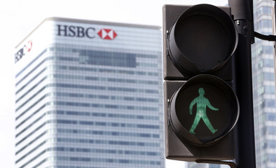 The HSBC building is seen in the background as the green man flashes at a pedestrian crossing in East London