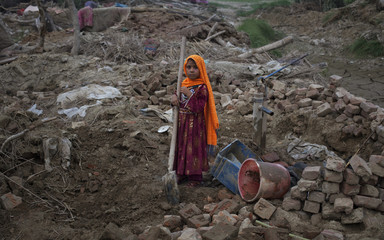 Bibi, a six-year-old Afghan girl, holds a shovel while assisting her family to excavate for belongings through their home damaged nearly two months ago by heavy floods near Nowshera Pakistan
