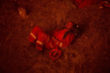 Inmate firefighter, lit by the glow of a backfire, rests while battling the Butte fire near San Andreas