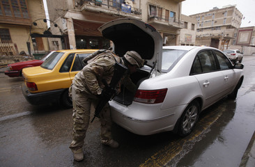 An Iraqi soldier searches a vehicle at a checkpoint in Baghdad