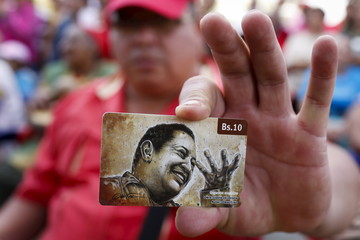 A man holds a prepaid telephone card, with an image depicting Venezuela's late president Chavez, during a ceremony to commemorate his 61st birthday at the 4F military fort in Caracas