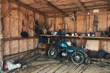 Old Blue-Green Motorbike In Picturesque Barn.Vintage Motorcycle In Old Hangar Against A Wall With Deer Antlers, A Bison Head And Many Interesting Rare Objects. Old Barn With Old Moped And Wooden Walls