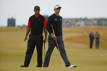 Tiger Woods and Adam Scott stand on the 12th green during the final round of the British Open golf championship at Muirfield in Scotland