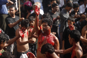 Shi'ite Muslims flagellate themselves during the Muharram procession ahead of Ashura, in front of a mosque  in Yangon