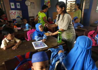 A parent feeds breakfast to her child during her first day at an Islamic kindergarten in a slum area in Jakarta