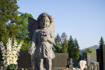 Statue of angel in cemetery during sunny morning. Slovakia