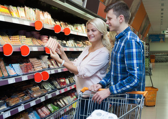 Young family couple choosing chilled sausages in shop