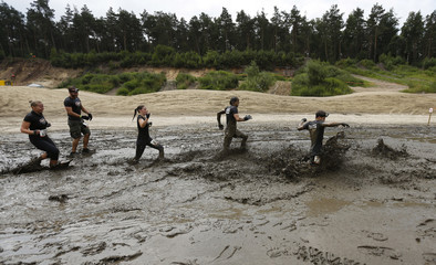 """Participants of """"Tough Mudder"""" endurance event series run through the """"Mud Mile"""" obstacle in the Fursten Forest"""