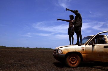Australian Aboriginal hunters Bruce and Robert Gaykamangu stand on the bonnet of their car looking for potential prey at a billabong near the 'out station' of Ngangalala, located on the outksirts of the community of Ramingining in East Arnhem Land