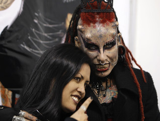 "Mexican tattoo and body modification artist  Maria Jose Cristerna, also known as ""Mujer Vampiro""  (Vampire Woman), poses for pictures with an attendee of the International Tattoo Convention in Bogota"
