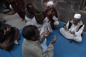 Neighbors pray outside the residence of 62-year-old heart patient Chaudhry Mohammad Gulab after he was buried in Lahore