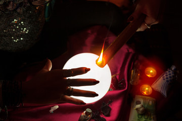Flame of candle and hand of fortune teller woman
