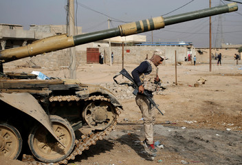 An Iraqi soldier jumps from a tank in a village outside Mosul