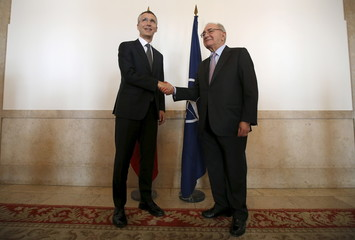 NATO Secretary-General Stoltenberg shakes hands with Portugal's Foreign Minister Machete before a news conference in Lisbon