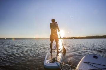 Standup paddler im Sonnenuntergang
