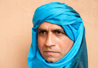 Portrait of a middle aged man standing in front of a mud wall in Morocco, Africa, wearing a blue Moroccan shesh, a Touareg turban.