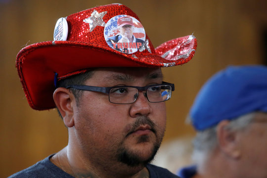 """A man with a red sequin cowboy hat and buttons waits for Republican nominee Trump to speak at """"Joni's Roast and Ride"""" in Des Moines"""