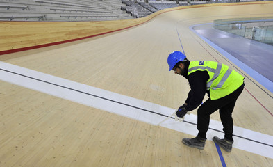 A construction worker removes masking tape on the finishing line of  the velodrome track at the London Olympic site in Stratford in east London