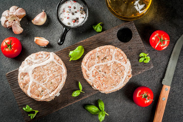 Raw organic meat. Chicken cutlets for burgers, with a grid of pork, for grilling or frying. With spices, basil, tomatoes, on a gray stone table on a cutting wooden board. Copy space top view