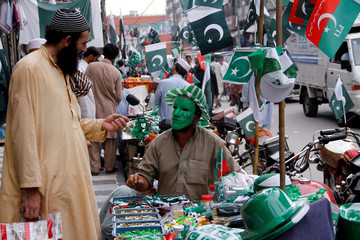 A vendor sells items with the colours of the Pakistani flag as people prepare to celebrate the country's Independence Day at a roadside stall in Peshawar