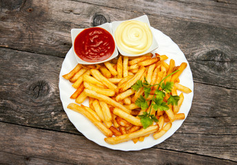 Top view on plate with french fries, tomato sauce and mayonnaise in small bowls