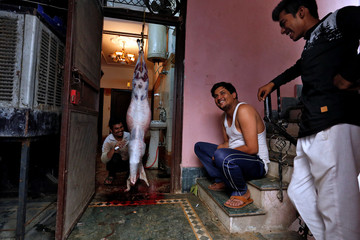 People share a joke as a goat is butchered in a house during Eid al-Adha in Delhi