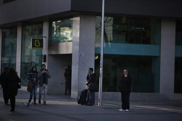 Men smoke outside a branch of Spain's Bankia bank in Madrid