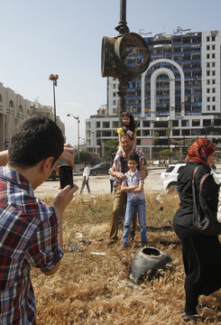 A boy takes photos of a man and his children at Old Clock square in Homs city