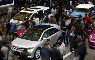 People look at Toyota cars during the 15th Shanghai International Automobile Industry Exhibition in Shanghai
