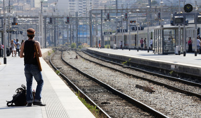 A commuter waits for a train during a nationwide strike by French SNCF railway workers at Marseille train station
