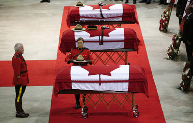 A Royal Canadian Mounted Police officer places a hat on one of three caskets during a regimental funeral for three fellow officers who were killed last week in Moncton